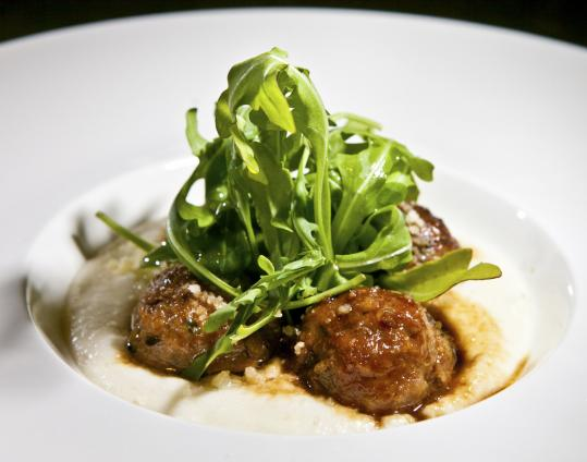 At Aragosta Bar + Bistro, braised veal and pancetta meatballs are served with soft polenta.