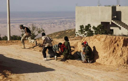 Rebel fighters in Libya took cover during clashes outside the city of Riyayna, southwest of Tripoli, yesterday. If the rebels take Zlitan, they would be within 85 miles of Tripoli.