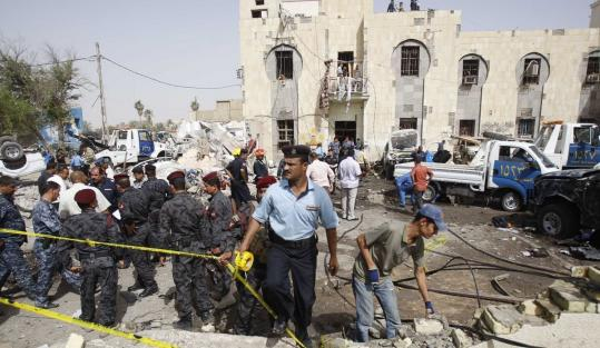 Security officials inspected the site of an attack Monday in Basra that killed five and injured 15.