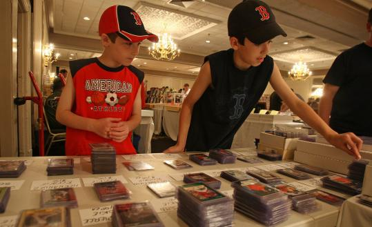 Representing a relatively rare age group, siblings Andrew and Jonathan Williams check offerings at last month's sports card show in Mansfield.