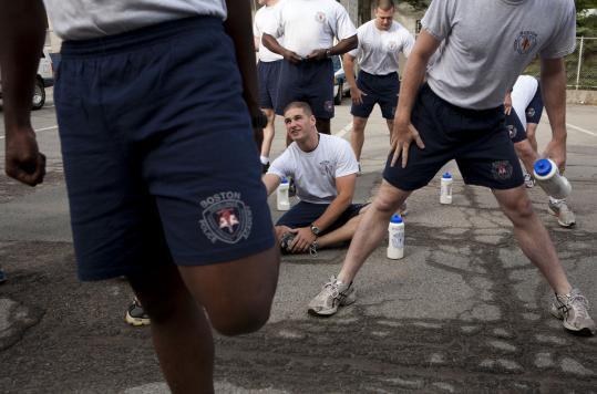 Boston Police Department recruits stretched yesterday before their last workout — a 9-mile run to police headquarters — at the Police Academy in Hyde Park before their graduation today.