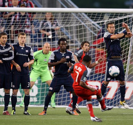 Toronto's Joao Plata shoots — in vain — over a wall of Revolution defenders last night.