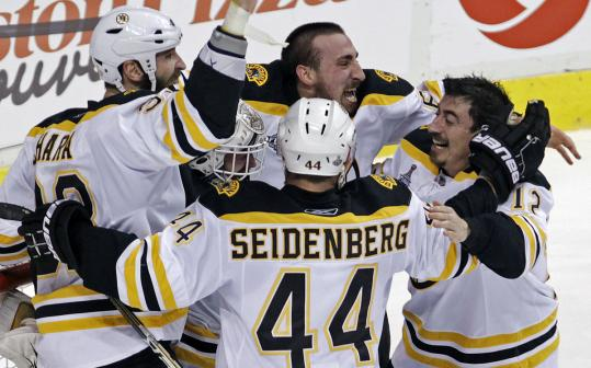 Bruins goalie Tim Thomas is mobbed by teammates after the final siren sounded at Rogers Arena.