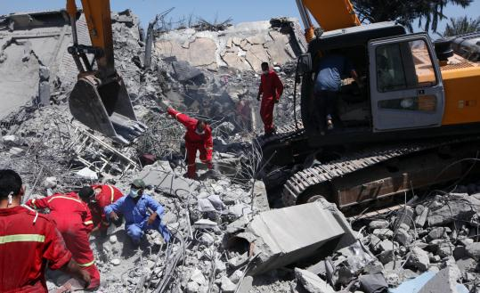 Foreign journalists were taken by government officials to the compound in Surman, where rescue teams yesterday inspected the two buildings that had been blasted to rubble.