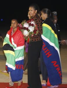 Michelle Obama's daughters, Sasha (left) and Malia, were given blankets when they landed in Pretoria last night; she received flowers.