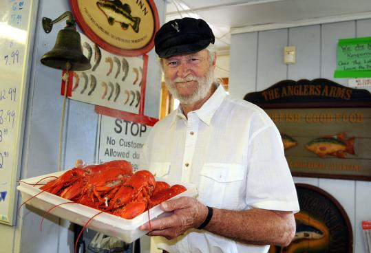 Hingham Lobster Pound owner Jack Daily holds a tray of boiled lobsters. The lobster meat will be used for the restaurant's signature lobster rolls.