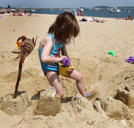 Zoe Guthrie, 4, works on a castle at M Street Beach.
