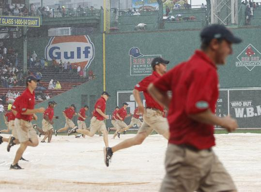 Yesterday's rain had the Fenway Park grounds crew on the run, as the tarp went on and off the diamond four times.