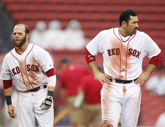 Playing baseball in the rain is a dirty job, but Red Sox Dustin Pedroia (left) and Adrian Gonzalez had to do it yesterday.