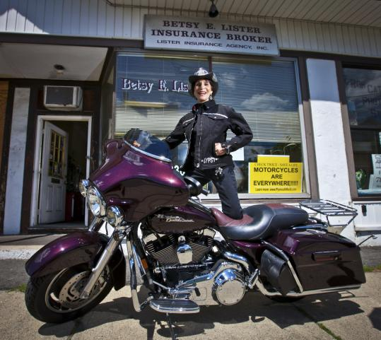 Betsy Lister with her Harley-Davidson Street Glide in front of her insurance agency in Medford.