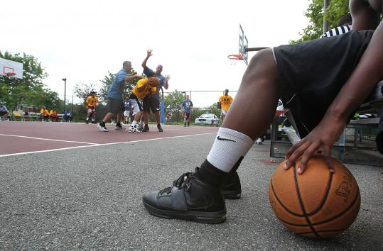 Demarius Dorsey, 14, watched police officers and local players battle for the ball during a game yesterday at Bromley-Heath.