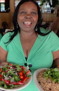 Lelene's chef-owner Juslène Louissant with platefuls of food;