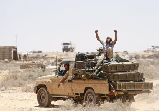 Libyan rebel fighters took a load from an ammunition depot government forces abandoned after it was bombed by NATO.