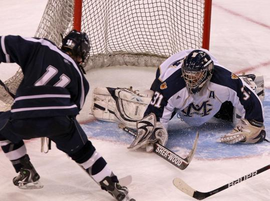 Malden Catholic goalie Patrick Young (right) turns aside a shot by St. John's Colin Blackwell in a game this March.