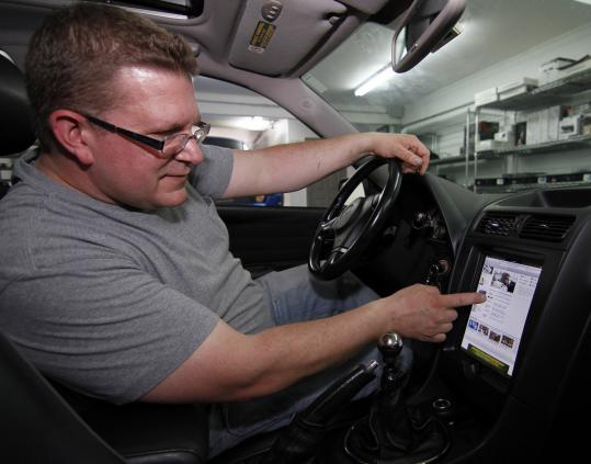 At Boston Mobile Concepts in Dedham, technician Kenyon Lee worked on a Lexus outfitted with an iPad.