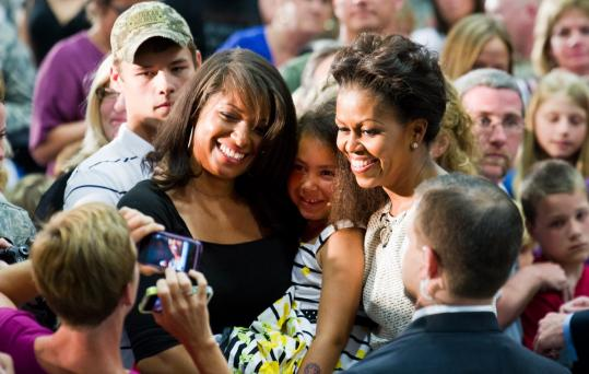 First lady Michelle Obama posed for senior airman Takara Matthews and her daughter Nami Cook, 6, both of Georgia, Vt., after speaking to Vermont military families in South Burlington.