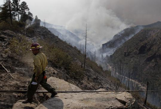 A firefighter from Las Vegas, N.M., held his ground on the flank of the massive wildfire near the nation's premier nuclear weapons laboratory in Los Alamos. Officials began planning for the return of thousands of residents and employees who fled.