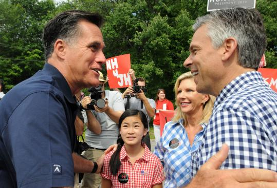 Republican presidential candidates Mitt Romney (left) and Jon Huntsman greeted each other yesterday in Amherst, N.H.