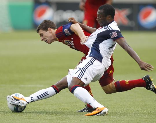 New England's Sainey Nyassi gets a step on Real Salt Lake's Will Johnson and steals the ball.