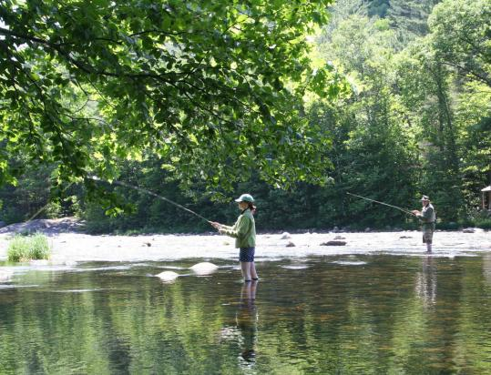 The author and her father, Drew Cammorata, fishing for trout in the Pemigewasset River in Lincoln, N.H.