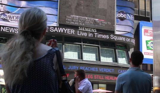 People stop and watch the verdict in the Casey Anthony trial on a screen in New York's Times Square.