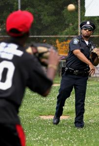 Little League pitcher Teshawn Coleman, 12, tossed a ball with Officer Dennis Simmonds yesterday at Harambee Park.
