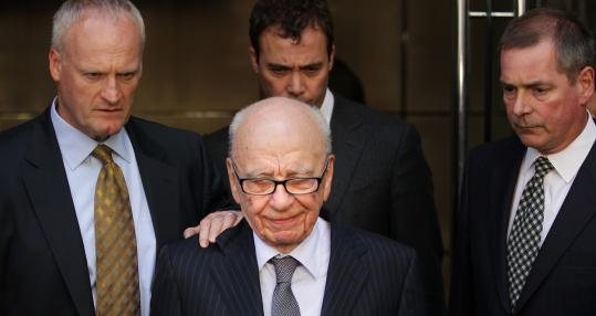Rupert Murdoch (center) left a hotel yesterday after apologizing to the family of a slain girl whose phone was hacked.