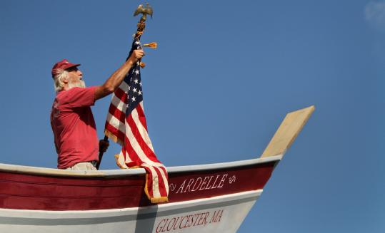 Steve Willard of Marblehead unfurls a flag on the new two-masted schooner Ardelle, just before its launch in Essex.