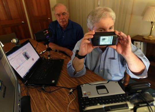 Peter Y. Flynn (left) and Sean Mullin of BI2 Technologies with the device designed to compare a suspect's biometrics against large databases.