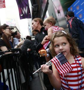 Rylie Rampone waits as mother Christie Rampone, captain of the US World Cup squad, is interviewed in Times Square.