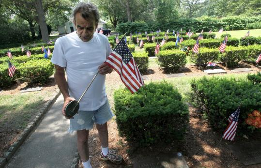 Bill Vegnani examined a grave marker at the Mt. Vernon Cemetery in Abington, where the copper and brass stems of veterans' flags and medallions have been stolen. Vegnani has tended the site for 20 years and said he has never seen a theft like this.