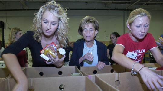 Myra Kraft's charitable efforts trickled down throughout the Patriots organization. In September 2007, Kraft (center) helped out at the Greater Boston Food Bank, with the fiancees of two of the team's players.
