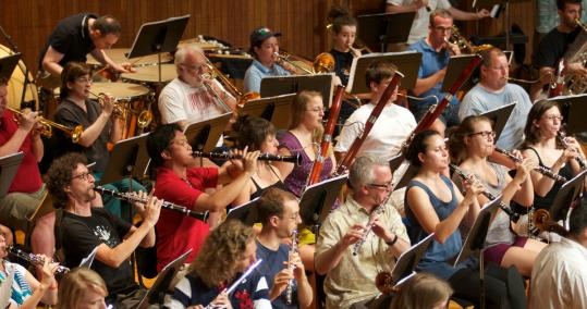 Members of the woodwind, brass, and percussion sections at a rehearsal of the Mercury Orchestra.