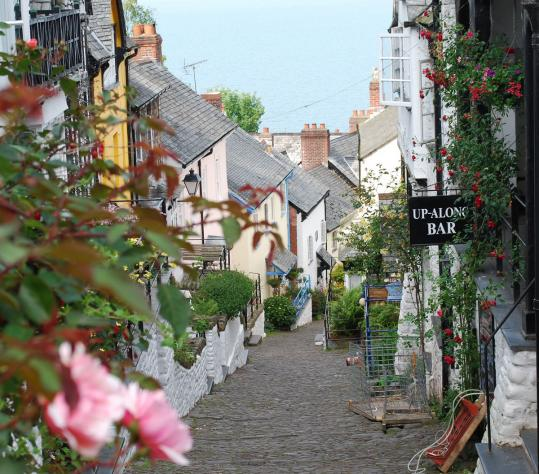 "Clovelly's famous cobbled High Street, known to residents as either the ""Down-Along'' or the ""Up-Along,'' meanders from the village cliff-top to its harbor on the Bristol Channel."