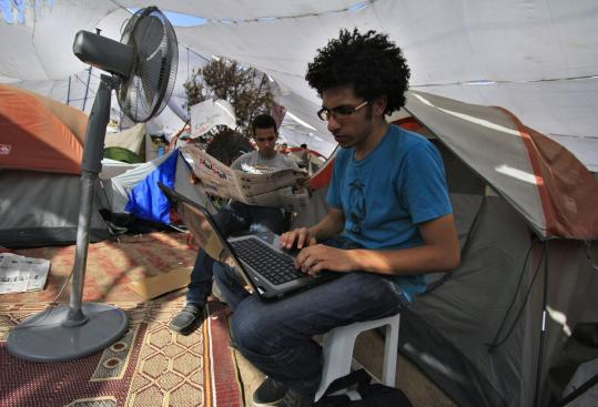 An Egyptian protester worked in a makeshift tent yesterday in Cairo's central Tahrir Square, where several hundred activists have gathered to keep up pressure on the military council ruling the country.