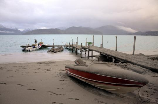 A boat covered with volcanic ash was docked on a lake in southern Argentina in June. A volcano in Chile has been spewing ash for six weeks, which has hurt tourism in neighboring Argentina.
