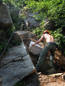 At left, Jeff Amari (top) and Dan Kurnick teamed up to move a boulder as part of the restoration of the Tuckerman Ravine Trail. The popular route on Mount Washington is under construction.