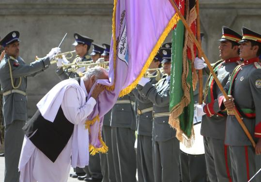 Ashraf Ghani, head of the Transition Commission, kissed the Afghan police flag in Bazarak, Afghanistan. Children tied to security forces are increasingly being targeted by insurgents.