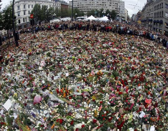 Mourners surround a sea of flowers in front of Oslo Cathedral yesterday.