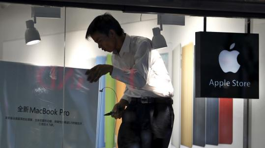 A man works on a poster at a shop masquerading as an Apple store in downtown Kunming in China.
