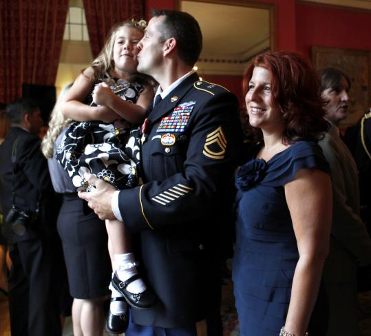 "DECORATED HEROES — Sergeant First Class Ryan Ahern, with his wife Gina, kissed his daughter Rhianne, 4, after he and five other members of the US Special Forces were presented the French ""Croix de la Valeur militaire"" for distinguished service in Afghanistan alongside the French Task Force Lafayette, at a ceremony yesterday in Washington."