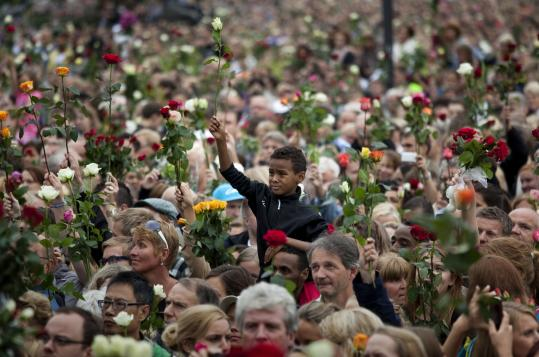 "Thousands of people gathered outside Oslo City Hall yesterday to participate in a ""rose march"" in memory of the victims of Friday's bomb attack and youth camp shooting massacre. Authorities now say eight people died in the bombing and 68, not 86, at the camp."