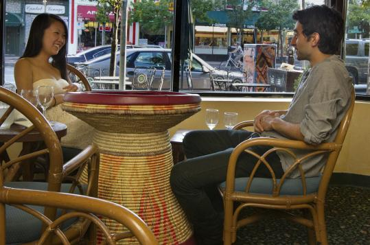 At Asmara Restaurant, Christin Wang and Andres Glimenakis sit at a mesop, the traditional Eritrean table.