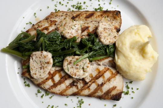 Grilled trout is served with mashed potatoes, greens, and pecan compound butter.