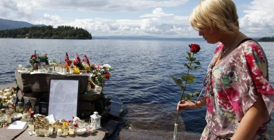 A woman paid her respects yesterday to the victims of Friday's killing spree, at a temporary memorial on Utoya. The police have been criticized for the seemingly slow pace of their response to the island attack.