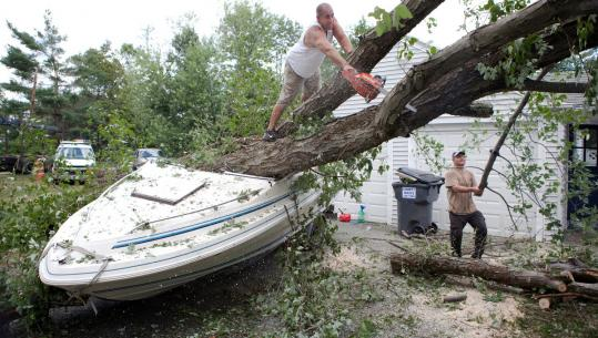 Anthony Trikas of Ludlow (left) and Barry Delamarter of Wilbraham cut up a fallen tree that crushed a friend's boat in Wilbraham.