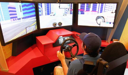 Kenny Codair, 18, of Hampton, N.H., steers a driving simulator along virtual city streets while learning lessons about distractions on the road.