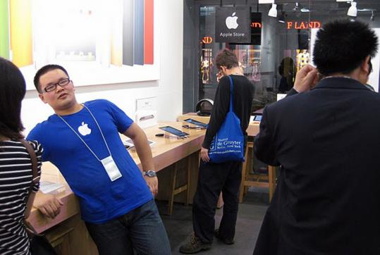 An employee wearing Apple's trademark blue T-shirt talks to a customer at an allegedly fake Apple store in Kunming.