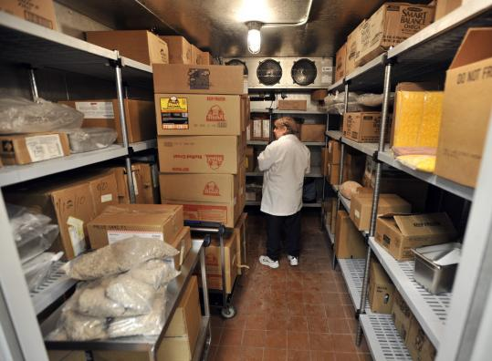A worker surveys food at Orchard Gardens Elementary School, one of four found to have expired food in their cafeterias.