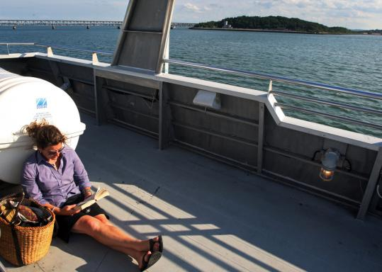 Kristen Webb of Scituate read on the upper deck of an MBTA ferry en route to Hingham on Thursday.